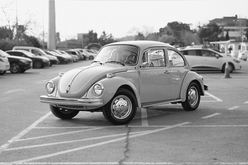 Black and white image of Volkswagen beetle in parking lot