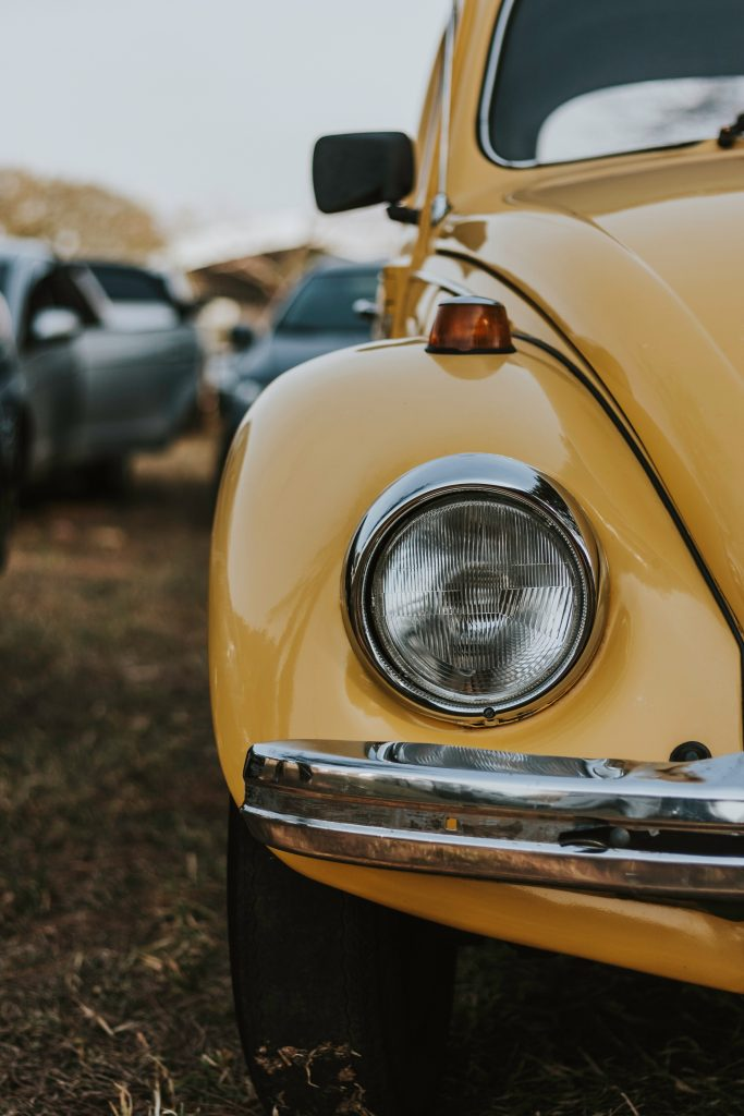 Front headlight of yellow Volkswagen Beetle