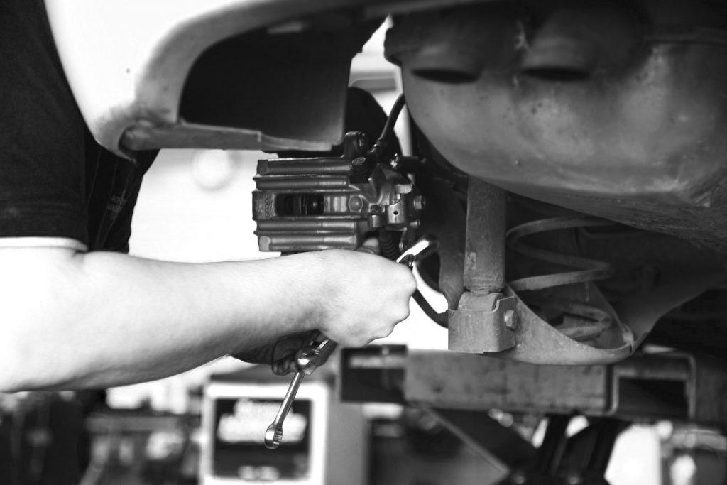 Mechanic repairing vehicle brakes